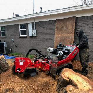 browns tree service worker using a stump grinding machine in fort worth tx